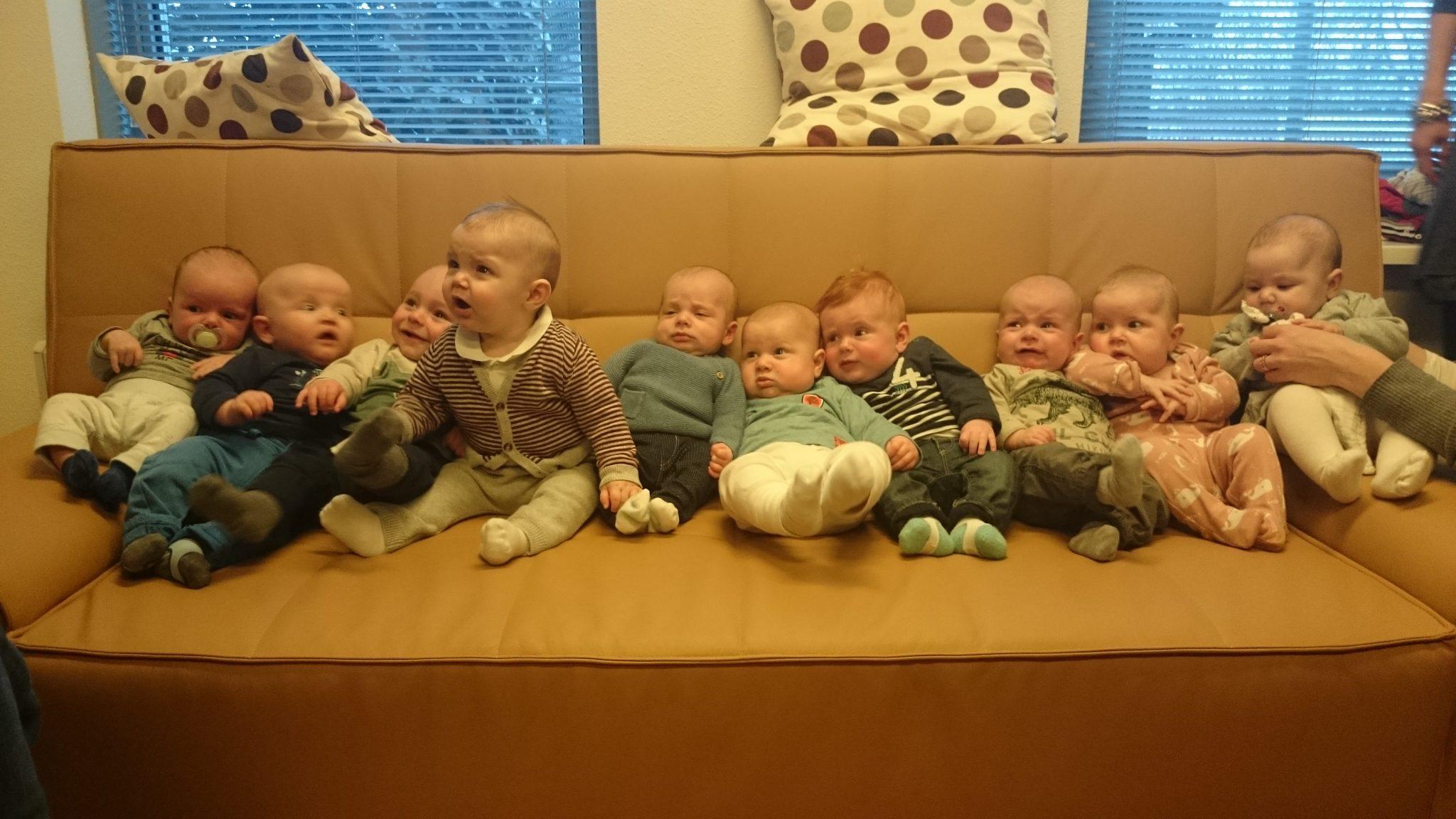 Tien baby's liggen naast elkaar op een bank.