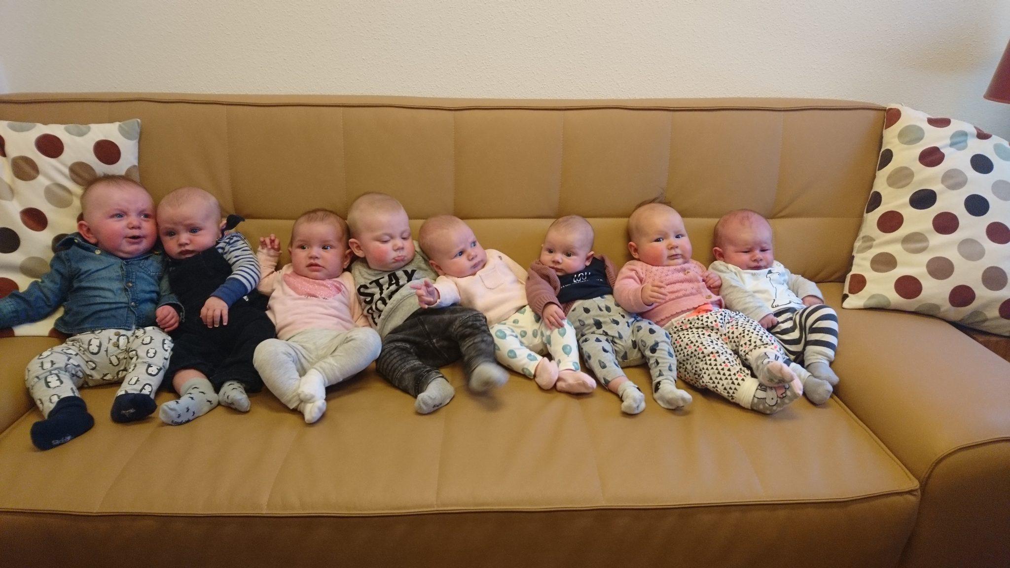 Acht baby's liggen naast elkaar op een bank.