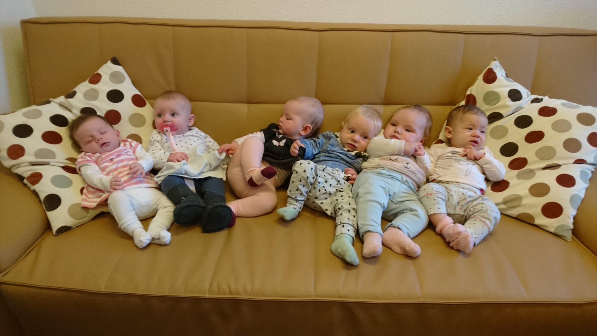 Terugkomdag zes baby's liggen naast elkaar op een bank