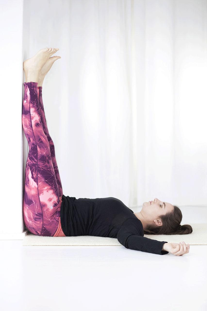 Vrouw ligt op haar rug met haar benen tegen de muur omhoog. Ontspanning